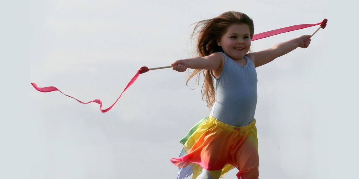 A little girl is going solo and is flying ribbons